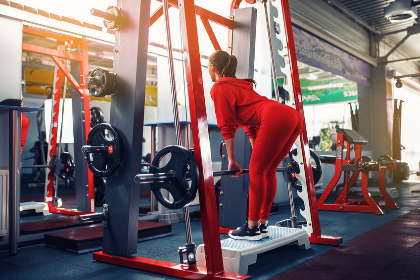 Women doing deficit pulls in a smith machine.