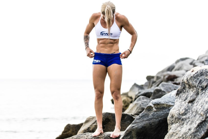Female athlete with six pack abs show result of using refeeds and diet breaks for weight loss