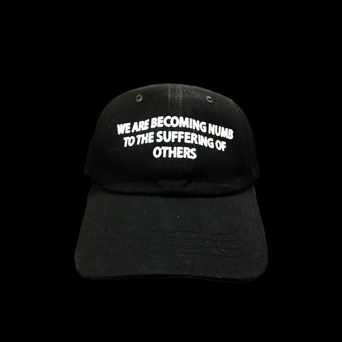 WE ARE BECOMING NUMB TO THE SUFFERING OF OTHERS CAP (BLACK)