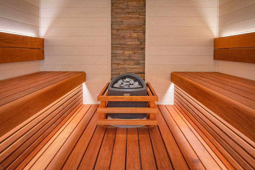Using a pale white timber on the sauna walls helps to brighten the space. The cladding is arranged horizontally which mirrors the benching and gives the eye a more inviting aesthetic, leading the centrepiece sauna heater.