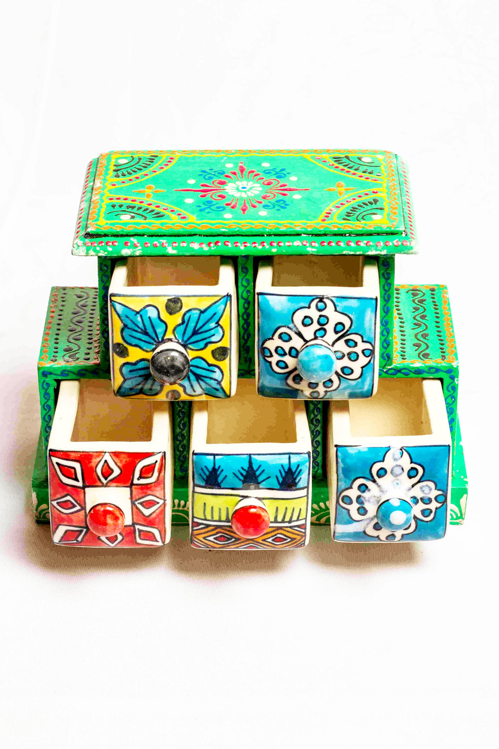 Chest of drawers in a green framed wooden box with painted motifs, with 5 ceramic drawers in green, red, and yellow