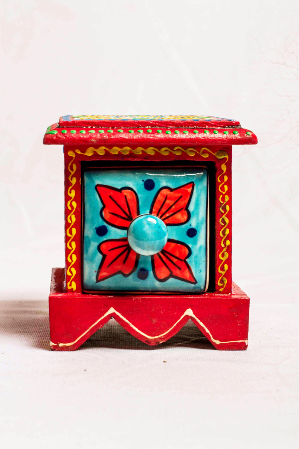 Single drawer in a red framed wooden box with painted motifs, with a ceramic drawer