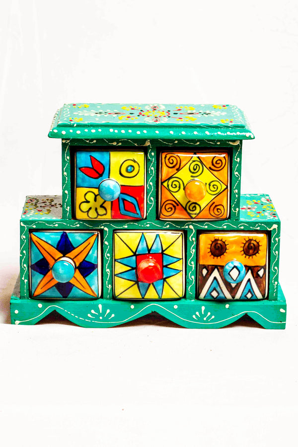 Chest of drawers in a green framed wooden box with painted motifs, with 5 ceramic drawers