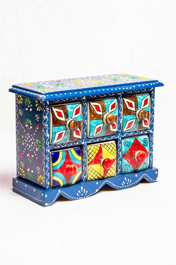 Chest of drawers in a blue framed wooden box with painted motifs, with 6 ceramic drawers