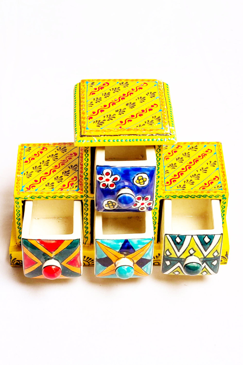 Four drawers in a yellow framed wooden box with painted motifs, with four ceramic drawers