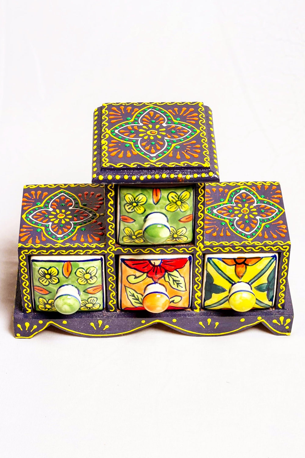 Four drawers in a black framed wooden box with painted motifs, with four ceramic drawers