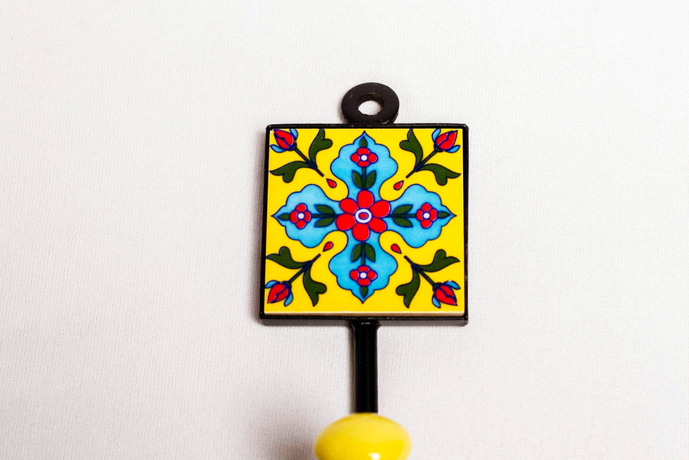 Metal and single ceramic tile wall hook, yellow with blue and red floral motif