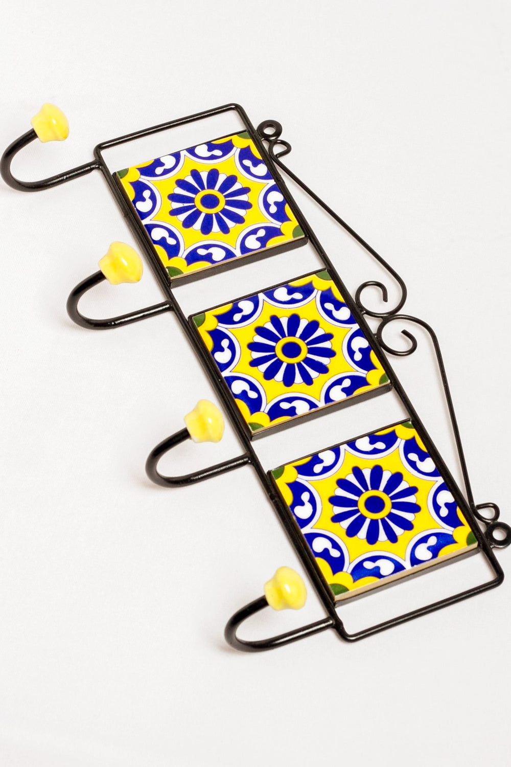 Metal and three ceramic tile with a 4 peg wall hook, yellow with blue and white floral motif