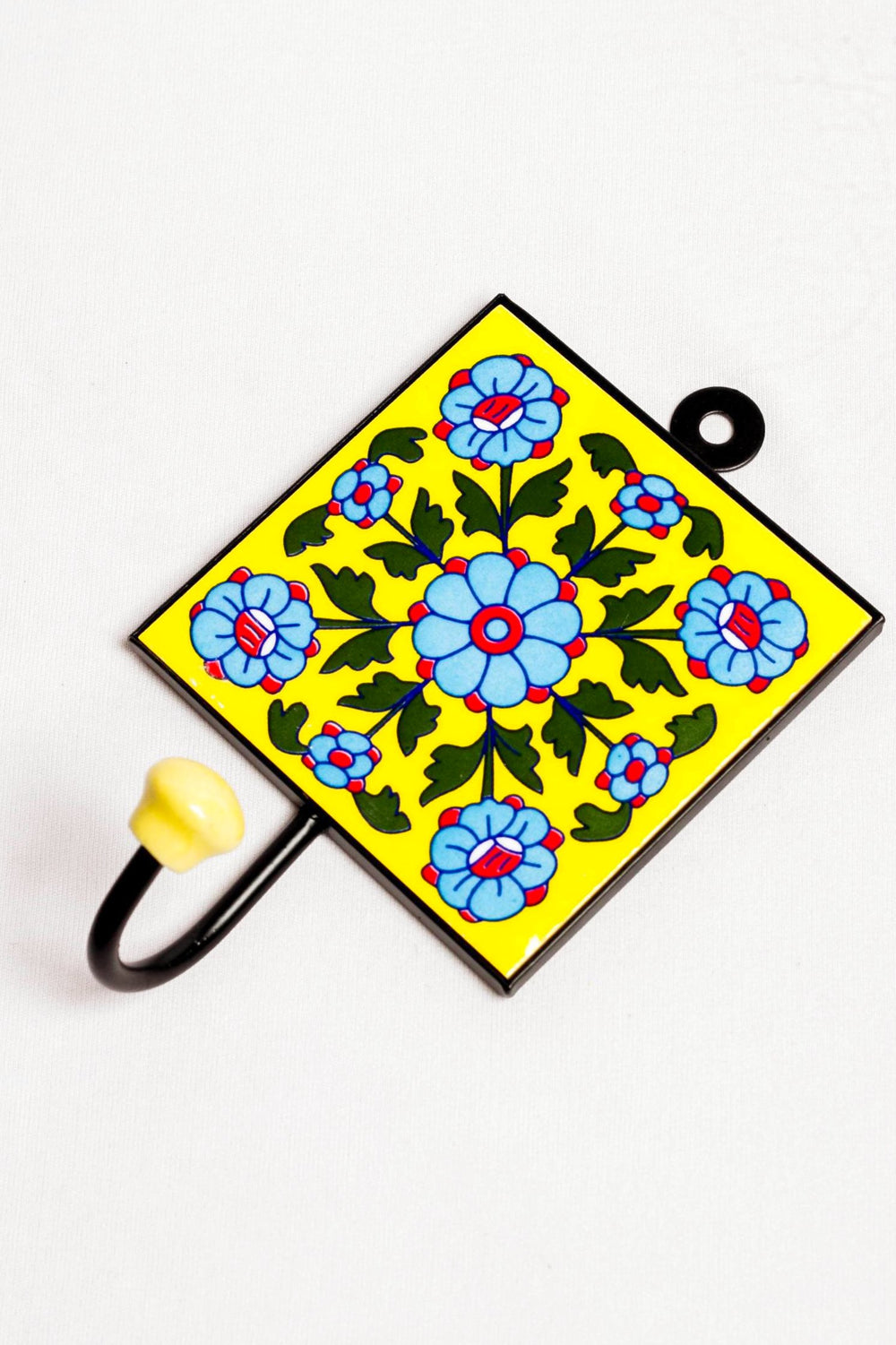 Metal and single ceramic tile with a peg wall hook, yellow with blue and red motif