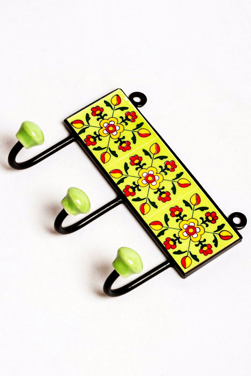 Metal and three ceramic tile with a 3 peg wall hook, green with yellow and red floral motif.