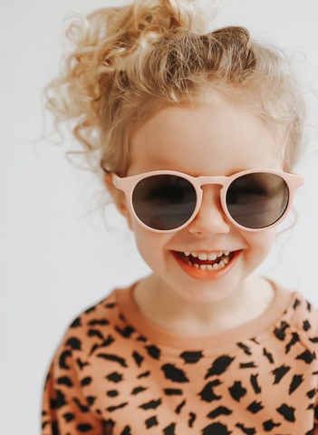 Child with blonde curly hair smiling and wearing pink sunglasses