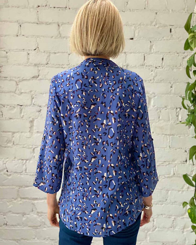 Woman in top with pleated detail at the front. Printed with blue and white cheetah on blue.
