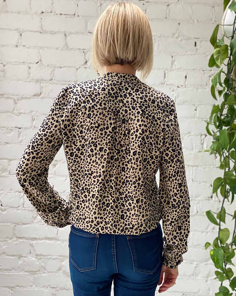 Woman in shirt style top printed in beige and black cheetah print.