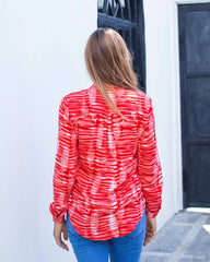 Woman in shirt style top with buttons all the way down the front. In a red and white peg tie dye print.