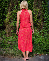 Woman in pink and orange printed dress with halter neck fastening and rouched waist.