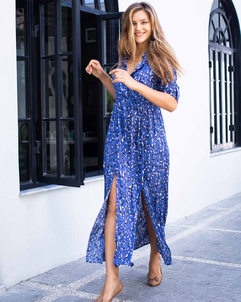 Woman in ankle length dress with two slits down the front. Printed with blue and white cheetah print on blue fabric.