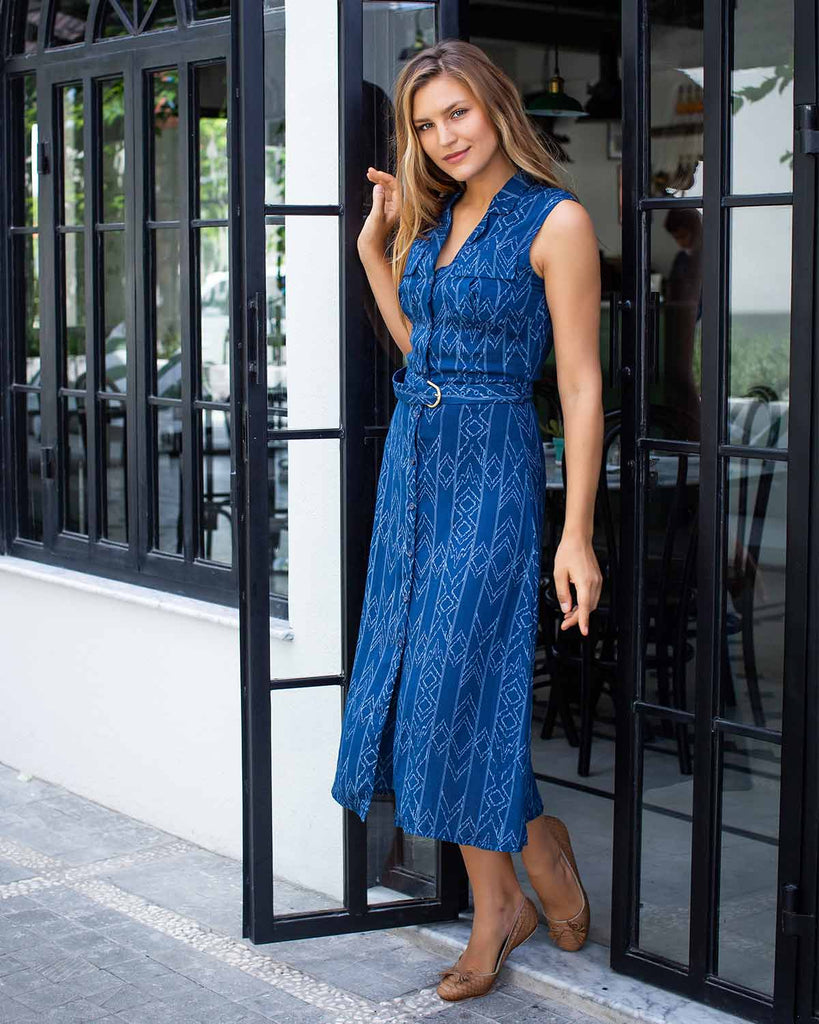 Woman in sleeveless, ankle length dress printed with white lines on dark blue. With a belted waist.
