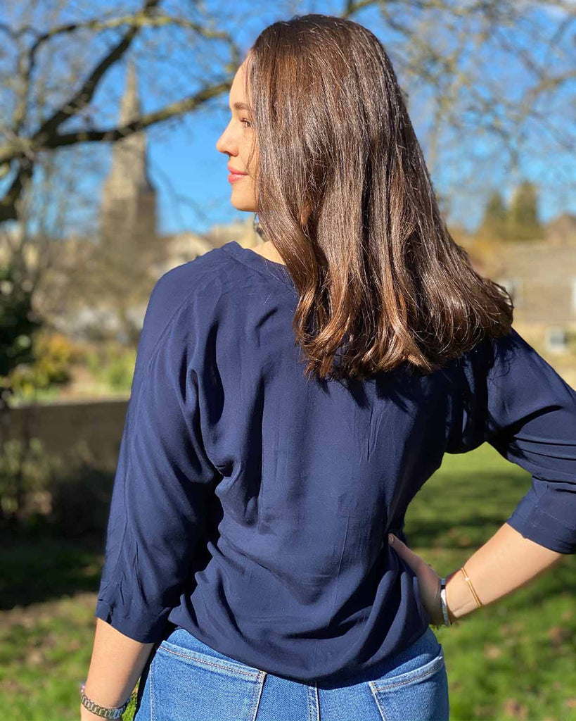 Woman smiling in plain navy top with 3/4 sleeve and elasticated bottom. It has pleats going down the front.