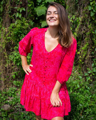 Woman in dress with button up front and 3/4 length sleeve. It comes above the knee and is in a hot pink fern print and v neck front.
