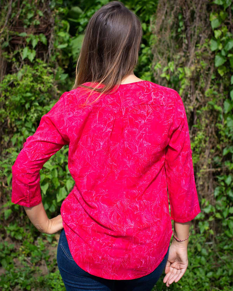 Woman in 3/4 sleeve top with V neckline, printed in hot pink fern print.