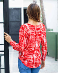 Woman in v neck top and long sleeves, printed in a red and white peg tie dye print.