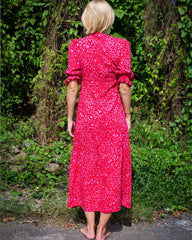 Woman in long dress with puff short sleeves, and wrap around waist. In a pink petal patterned print.