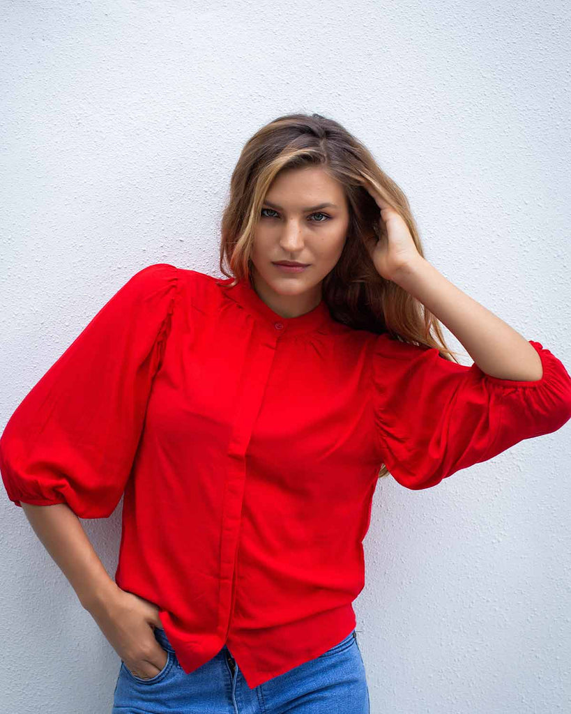 Woman in a red top with cuffed 3/4 sleeves and a top to bottom button fastening, in a poppy red colour.