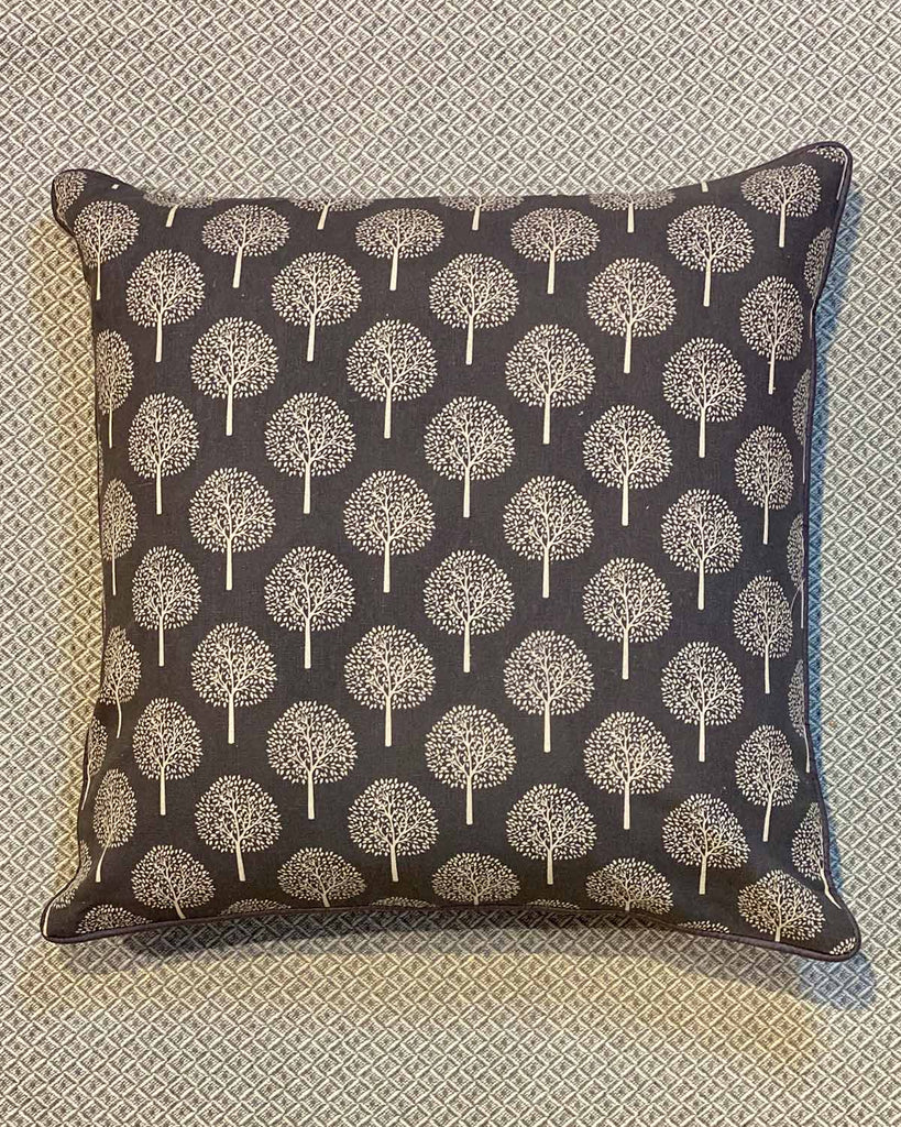 One cushion printed with lots of white mulberry trees on grey.
