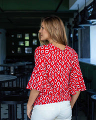 Woman in a printed top with a puff sleeve, the print is a hand designed white print in a shape of a sweet pea.