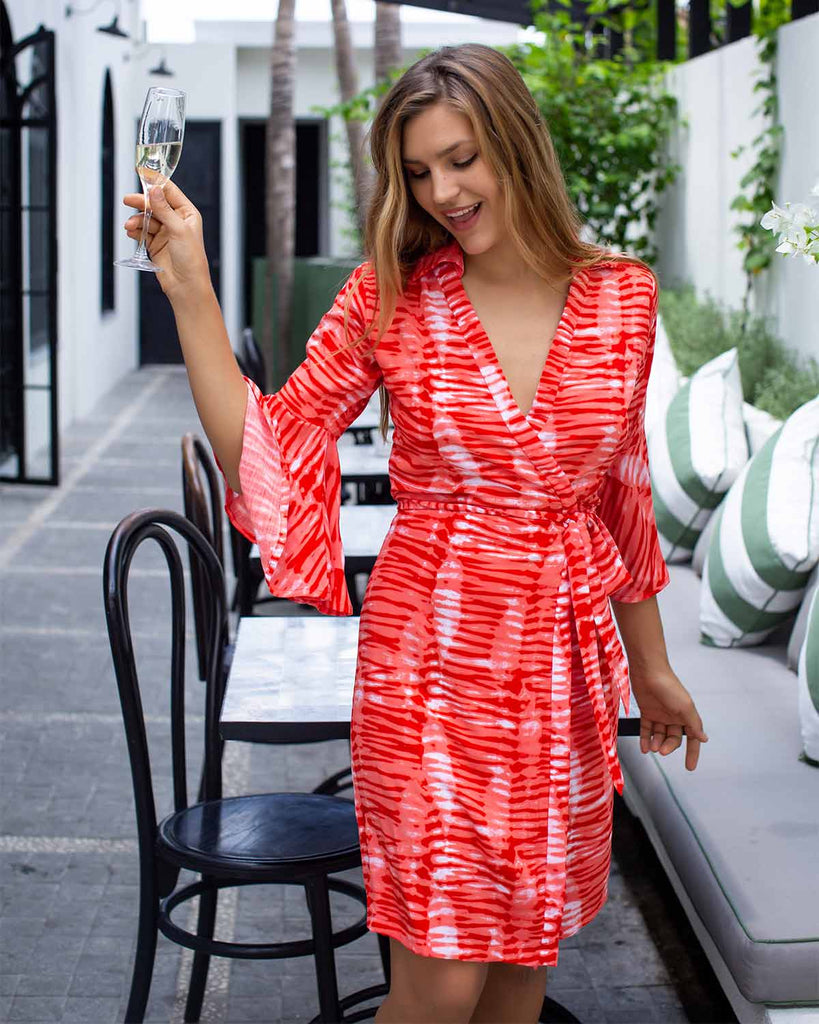 Woman in wrap dress with bell sleeves, printed in a red and white peg tie dye print.