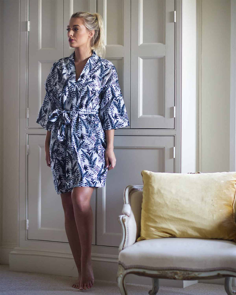 Woman in bedroom in grey leaf printed sleep robe with tie waist.