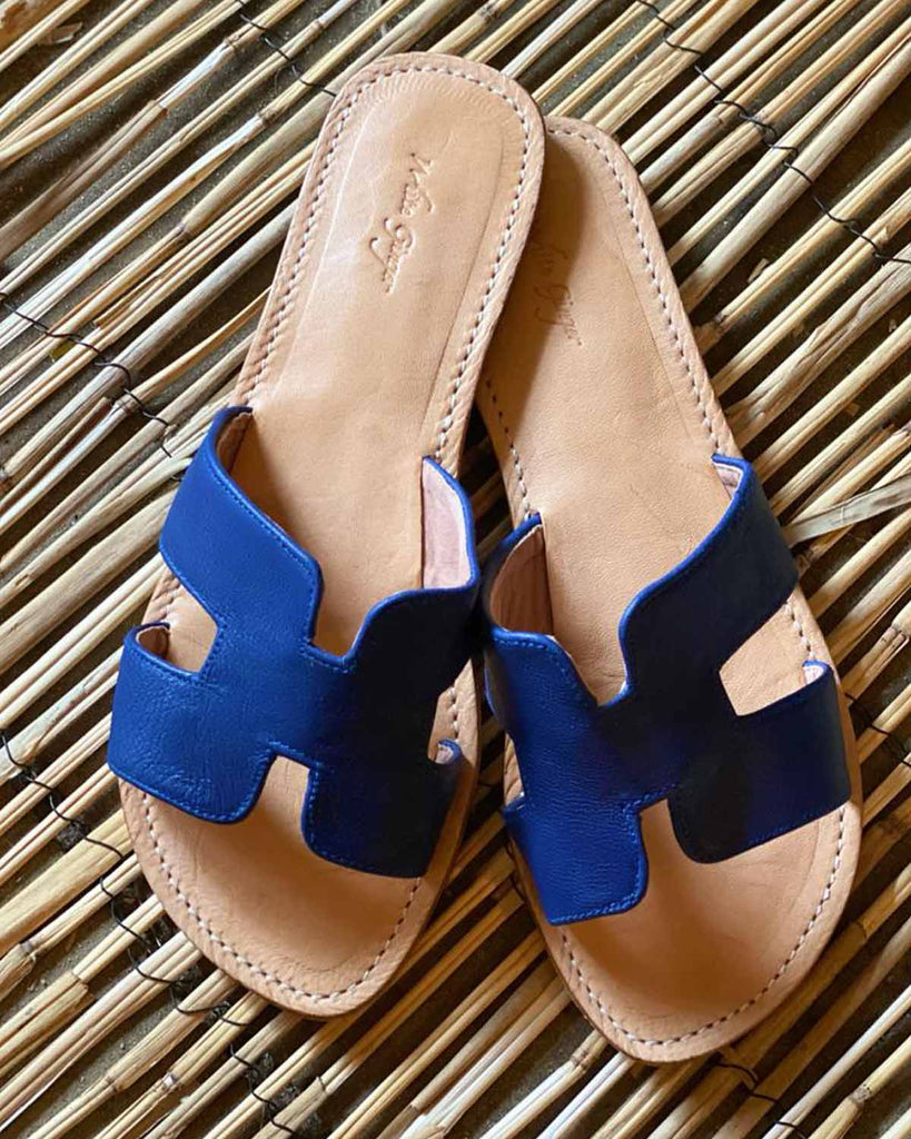 Woman in her fashion accessory, navy sliders made from 100% leather. The style is in a H design.