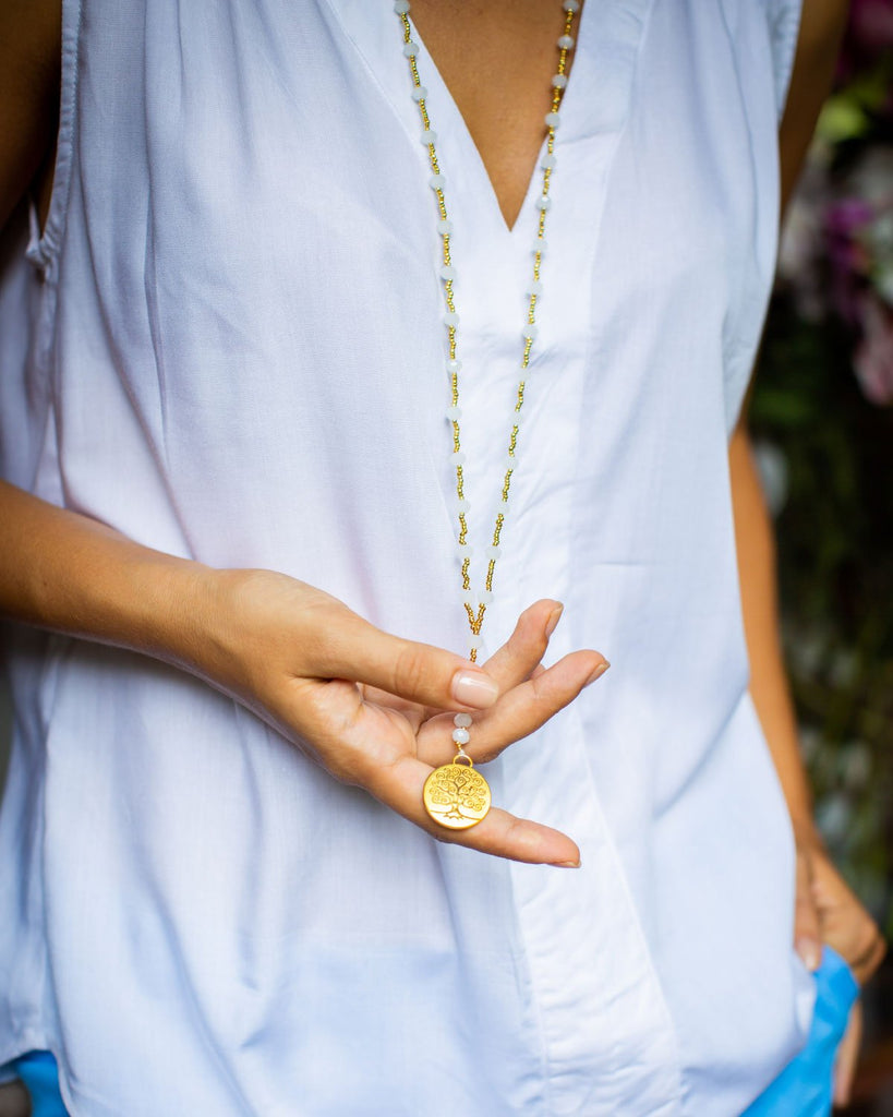 Woman holding a white crystal necklace with a tree of life pendant, with white shirt.