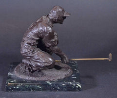 picture of a bronze golf sculpture of a male eyeing the green
