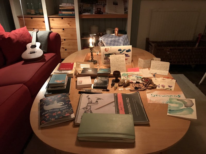 A scene of my altar table on retreat, with many small books and pieces of art, a candle, and a ukelele