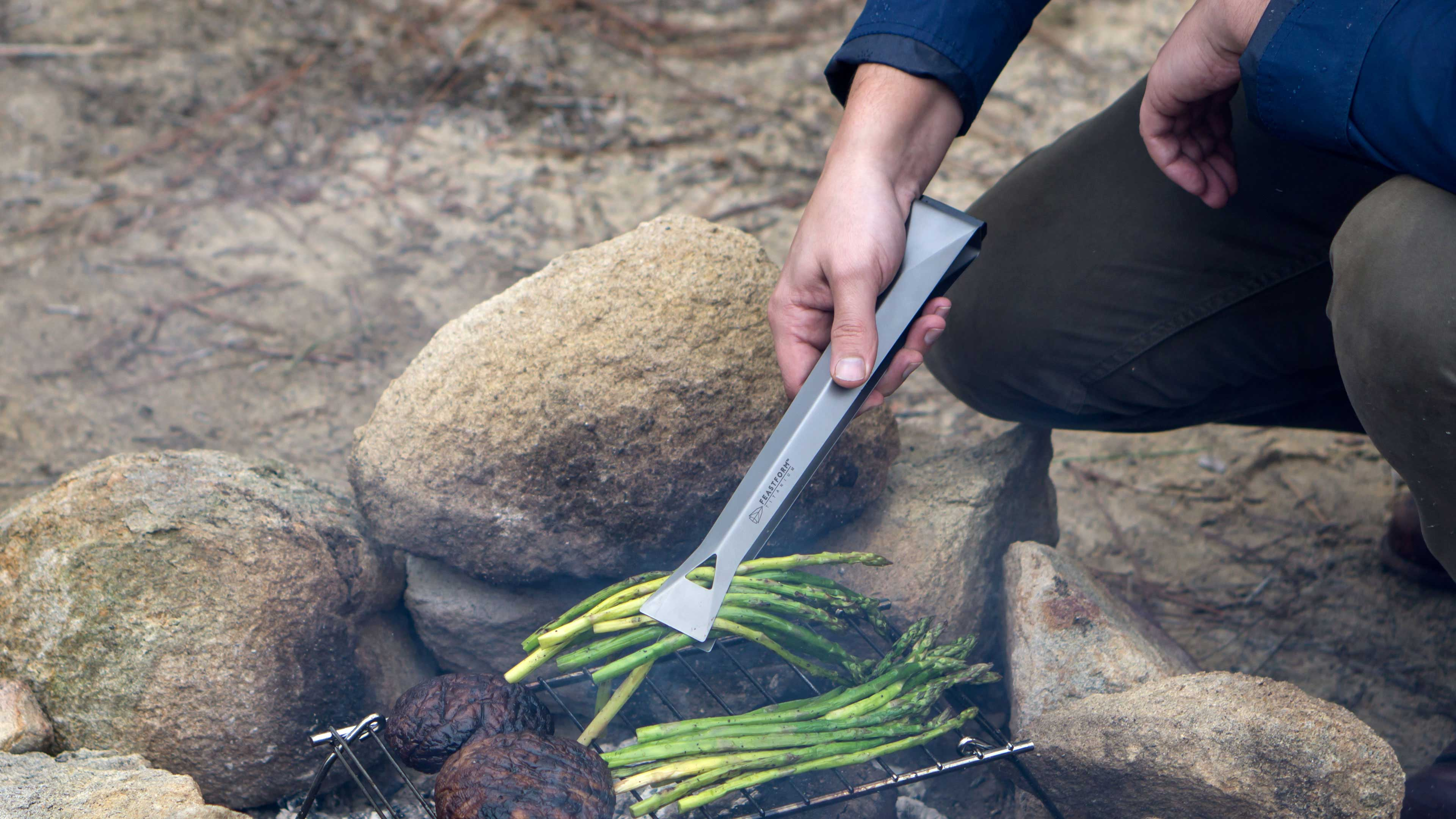 Assembled Feastform titanium camping tongs in use.