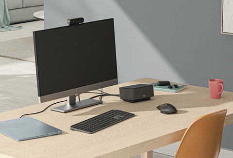 Logi Dock on a desk, connected to a computer, with a wireless mouse and keyboard visible on the desk in front of a monitor