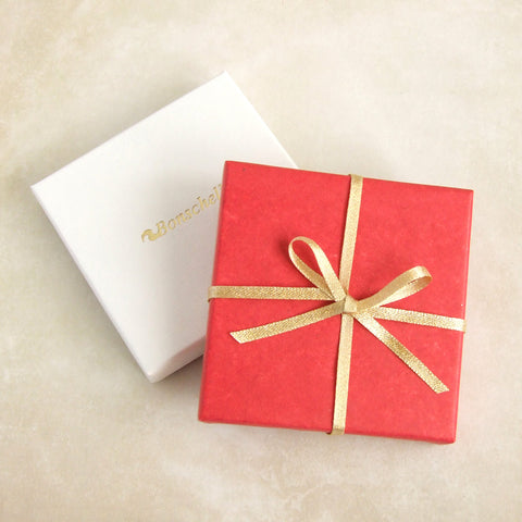 Bonschelle gift wrapped box with red tissue and gold bow