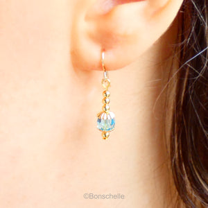 Handmade dangle earrings made with turquoise coloured Swarovski cut glass crystal faceted beads, small gold toned beads and 14K gold filled earwires shown being worn.