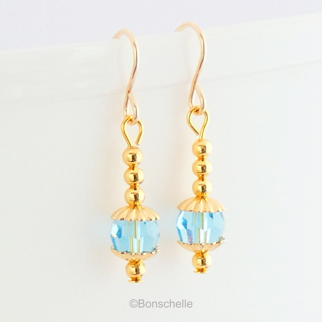Handmade dangle earrings made with turquoise coloured Swarovski cut glass crystal faceted beads, small gold toned beads and 14K gold filled earwires.
