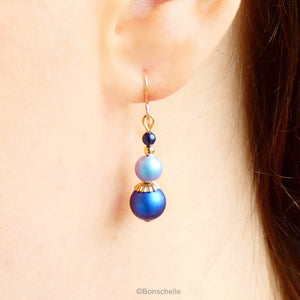 Blue swarovski crystal pearl beaded drop earrings with 14K gold filled earwires for women with gold accents shown worn on an ear