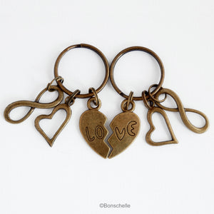 antique bronze toned set of metal keyrings for a couple, each one has one half of a love heart and the word Love, with an open heart charm and a number 8 charm.