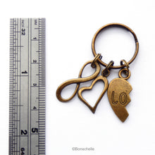Load image into Gallery viewer, one half of the set of antique bronze toned  metal keyrings for a couple, with half a love heart and the word Love, with an open heart charm and a number 8 shown to scale with a ruler. charm.