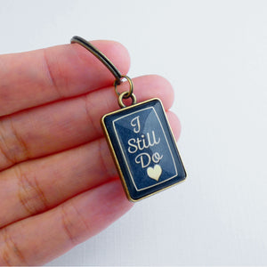 A double sided bronze and navy blue rectangle keyrings showing the front side with  the words 'I still do'