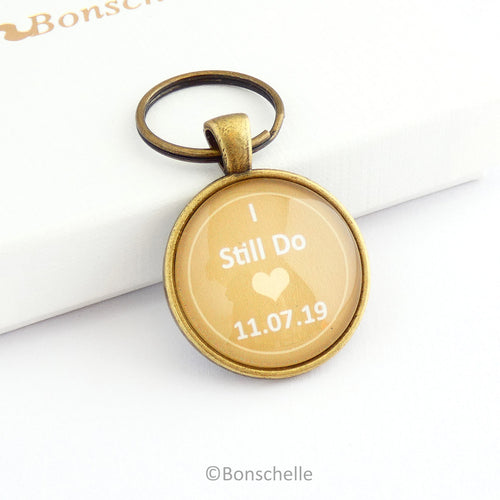 Round bronze toned wedding anniversary keyring gift with the words I still Do, a small heart and a custom date