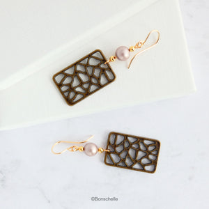 Handmade earrings made with rectangular shaped antique bronze filigree style charms, Swarovski simulated pearls in a light almond shade, gold toned beads and 14K gold filled earwires.