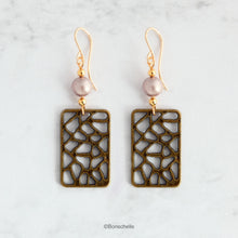 Load image into Gallery viewer, Handmade earrings made with rectangular shaped antique bronze filigree style charms, Swarovski simulated pearls in a light almond shade, gold toned beads and 14K gold filled earwires.