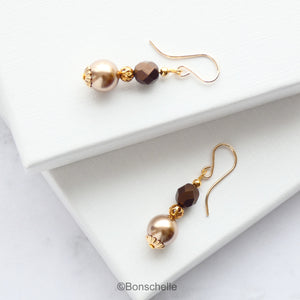 Handmade earrings made with light bronze swarovksi simulated pearls, dark bronze faceted glass beads, small gold toned beads and 14K gold filled earwires. shown laying on a surface