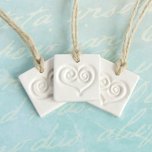 3 square white clay gift tag ornaments with heart imprint and jute ribbon