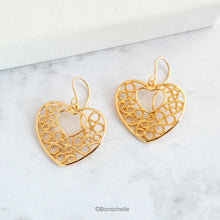 Load image into Gallery viewer, 18K gold plated filigree heart earrings with 14K gold filled earwires shown on a surface